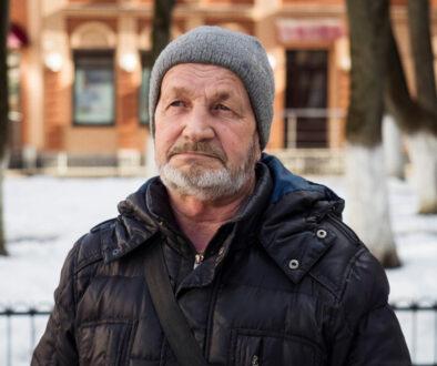 Elderly sad tired man on a city street in winter, real people ev