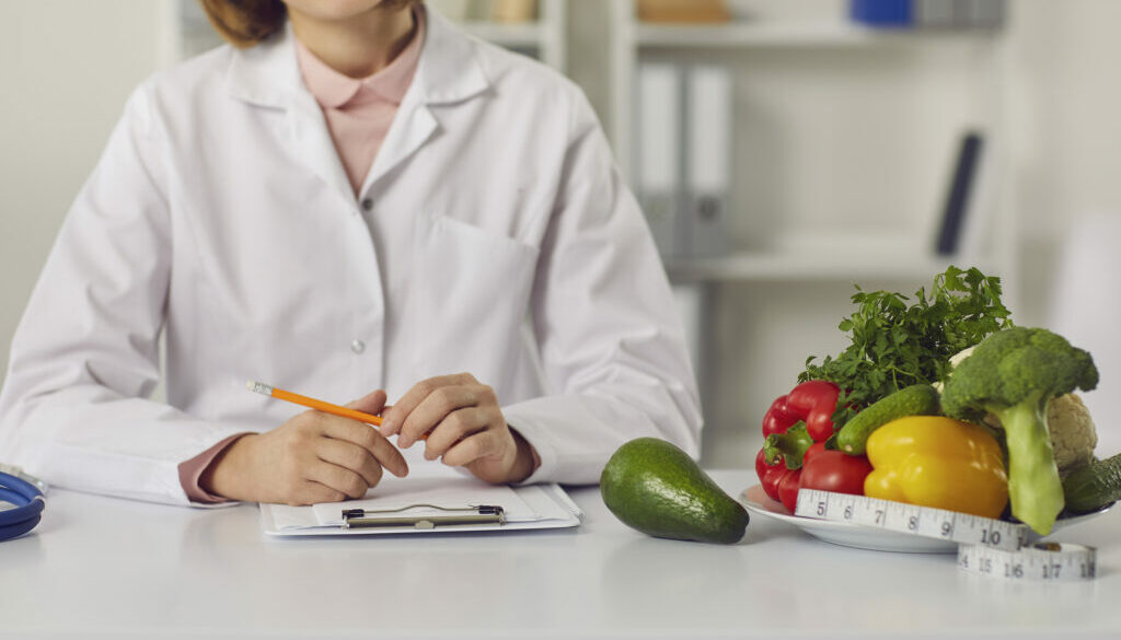Dietitian Sitting At Table With Fresh Fruit, Vegetables And Indi